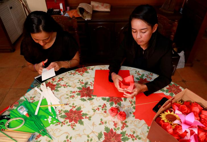 Filipino entrepreneurs Ann Rodrigues and Alex Castro make origami flowers to be sold ahead of Valentines Day