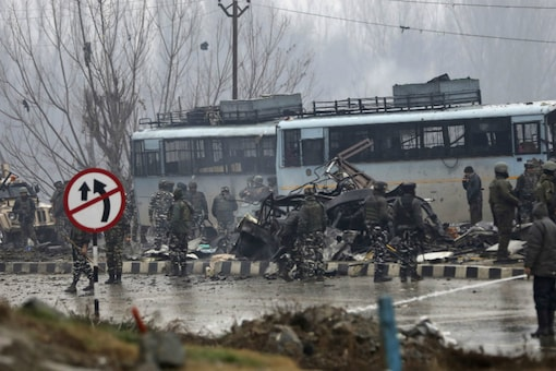 Paramilitary soldiers stand by the wreckage of the CRPF bus after the attack in Kashmir's Pulwama on Thursday. (AP)