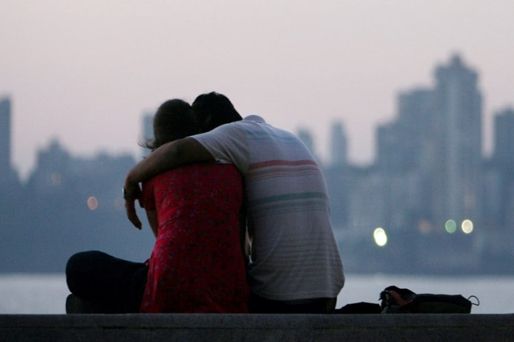 A couple sits on the seafront on the eve of Valentine's Day in Mumbai