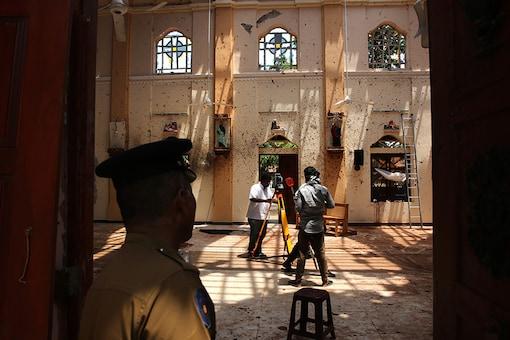 A policeman stands guard, as surveyors work at St. Sebastian's Church. (Image: AP)