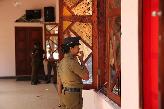 A Sri Lankan policewoman looks at the damage inside St. Sebastian's Church. (Image: AP)