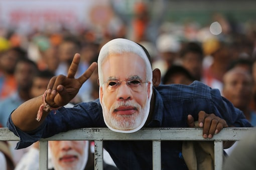 A supporter of BJP wears a face mask featuring Prime Minister Narendra Modi during an election campaign rally of in Hyderabad. (Image: AP)