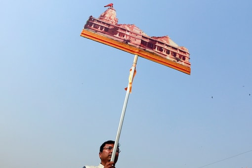 """A supporter of the Vishva Hindu Parishad (VHP), a Hindu nationalist organisation,  carries a cutout of a proposed Ram temple that Hindu groups want to build at a disputed religious site in Ayodhya, during """"Dharma Sabha"""" or a religious congregation organise"""