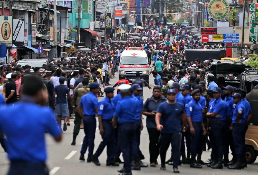 Sri Lankan police officers clear the road as an ambulance drives through carrying injured of Church blasts in Colombo, Sri Lanka. (Image: AP)