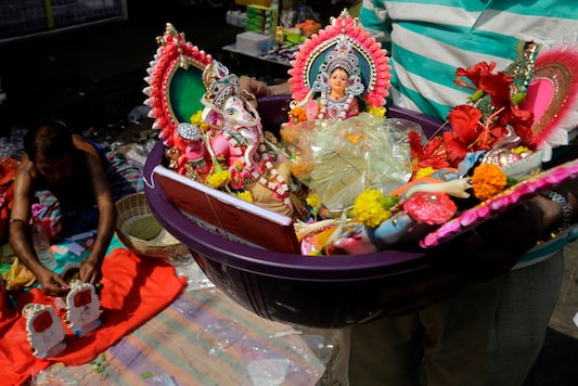 A devotees carries a basket with idols of lord Ganesha and goddess of wealth Lakshmi to perform rituals on Bengali New Year in Kolkata. (Image: AP)