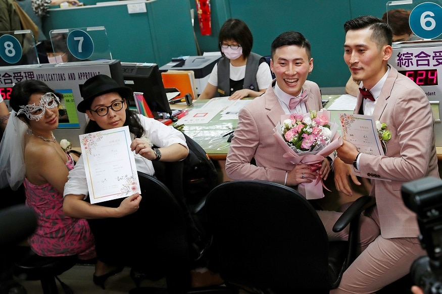 Couples Li Ying-Chien and Cynical Chick, and Marc Yuan and Shane Lin, pose for photographs after registering for same-sex marriage at the Household Registration Office in Shinyi District in Taipei