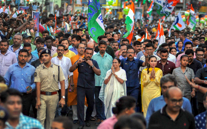 Trinamool Congress supremo Mamata Banerjee with Bengali film actress and party candidate from Jadavpur Parliamentary constituency Mimi Chakraborty, during a roadshow for the last phase of Lok Saha polls, in Kolkata. (Image: PTI)