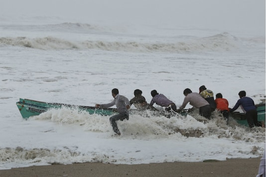 File photo of fishermen moving their boat from the rough sea waters to a safer place off the Veraval coast in Gujarat on Thursday.