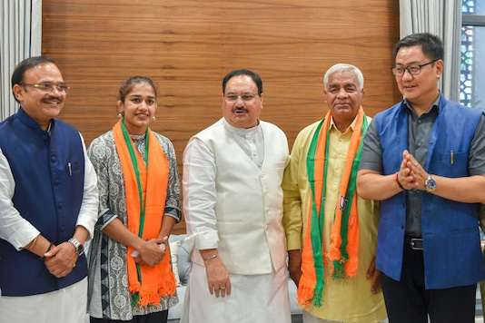 BJP Working President JP Nadda and Union Minister Kiren Rijiju pose for a photograph with the wrestler Babita Phogat and her father Mahavir Singh Phogat after they joined the Bharatiya Janata Party at BJP headquarters, in New Delhi. (Image: PTI)