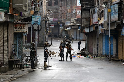 Paramilitary soldiers stand guard on a deserted street during curfew in Srinagar. (AP Photo/Dar Yasin, file)