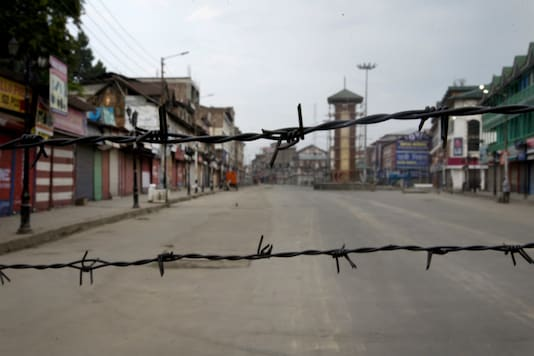 In this August 6, 2019 file photo, a deserted street is seen through a barbwire set up as blockade during curfew in Srinagar. (AP)
