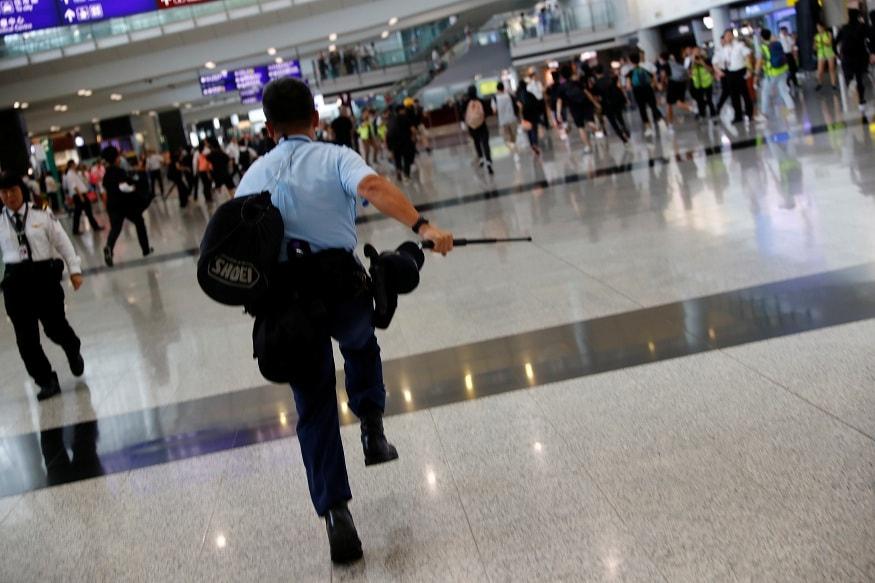 A police officer chases a flashmob inside Hong Kong International Airport, Hong Kong, China