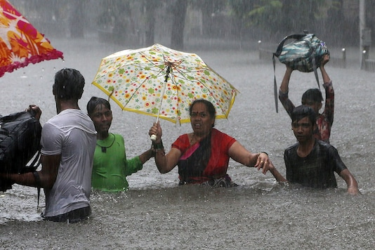 People hold hands and navigate their way through a flooded street as it rains in Mumbai. Incessant rainfall has resulted in flooding in many parts of the city, disrupting traffic movement and daily life in the city. (Image: AP)
