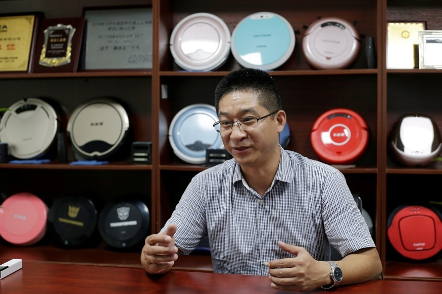 Terry Wu, deputy general manager of Matsutek, speaks next to robot vacuum cleaners on display during an interview in Shenzhen
