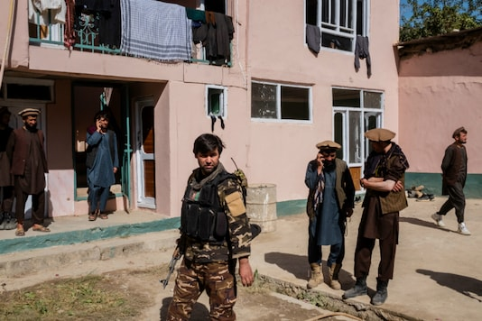 An Afghan soldier, center, and a group of alleged Taliban fighters in the courtyard of an intelligence service guesthouse in Fayzabad, Afghanistan (File photo: NYT)