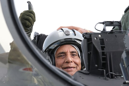 Rajnath Singh gestures as he sits in a Rafale jet fighter during an handover ceremony at the Dassault Aviation plant in Merignac,France. (Image: AP)