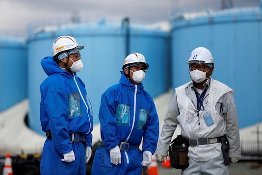 Workers are seen in front of storage tanks for radioactive water at Tokyo Electric Power Co's (TEPCO) tsunami-crippled Fukushima Daiichi nuclear power plant in Okuma town, Fukushima prefecture, Japan February 18, 2019. Picture taken February 18, 2019.   (Image: REUTERS)