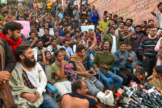 JNU students and their leaders who got injuries in police lathicharge shout slogans during a press conference at the university campus in New Delhi. (Image: PTI)
