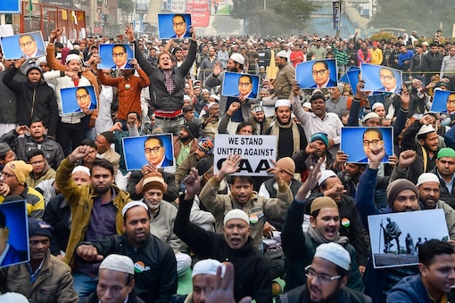 File Photo: Protesters hold placards during a demonstration against the Citizenship Amendment Act (CAA) at Jamia Nagar in New Delhi. (PTI Photo)