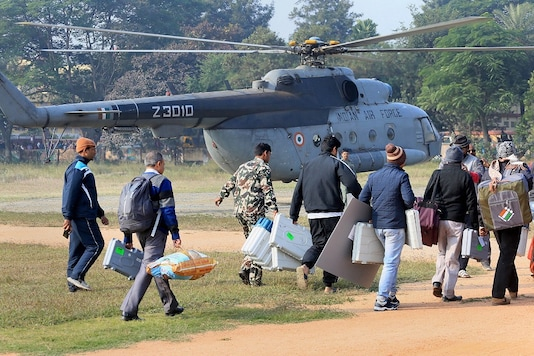 Polling personnel carry their equipment as Jharkhand Armed Police (JAP) jawans keep vigil at a helipad during Jharkhand assembly election in Hazaribagh. (PTI File)
