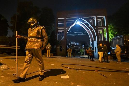 Policemen stand guard near Jamia Millia Islamia following the protests against Citizenship Amendment Act, in New Delhi, on Sunday. (PTI)