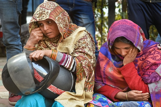 Family members of victims of a fire at a factory in Rani Jhansi Road wait outside the mortuary of Lok Nayak Hospital in New Delhi on Sunday. (PTI)