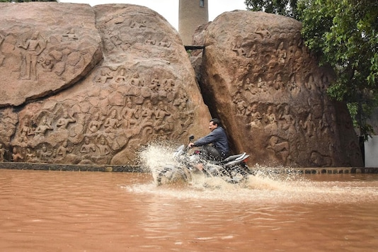 A man rides a motorcycle through a waterlogged road after heavy rains, at the heritage site of Mamallapuram, December 1, 2019. (Image: PTI)