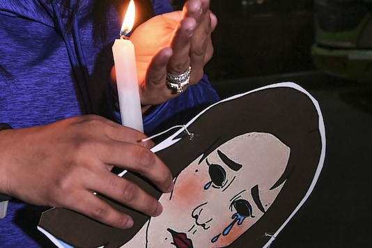 Indian Youth Congress (IYC) activists hold a candlelight march demanding justice for rape victims at UP Bhawan in New Delhi on Saturday. (PTI)