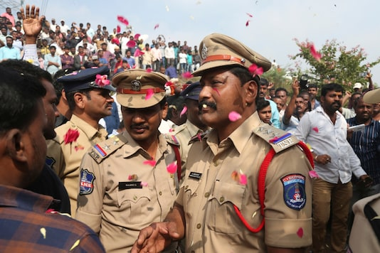 People throw flower petals on the Indian policemen guarding the area where rape accused were shot in Hyderabad (AP)