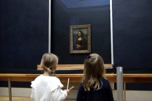 Two youg girls look at the painting Mona Lisa (La Joconde) by Leonardo Da Vinci as it returns in the gallery where it is normally displayed, after works on the color of the walls and and a new glass screen, at the Louvre museum in Paris, France, October 7, 2019. REUTERS/Philippe Wojazer