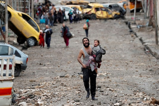 A man cries as he carries his daughter while walking from an Islamic State controlled part of Mosul towards Iraqi special forces soldiers during a battle in Mosul, Iraq. (Image: Reuters)