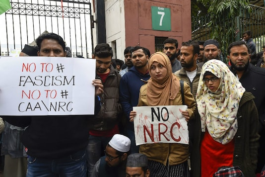 File photo: Students along with general members of the public hold placards against NRC and Citizenship Amendment Act outside Jamia Millia University. (PTI)