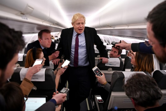 Britain's Prime Minister and Conservative leader Boris Johnson talks with journalists as he travels aboard a plane bound to Birmingham, Britain, December 9, 2019. (Ben Stansall/Pool via REUTERS)