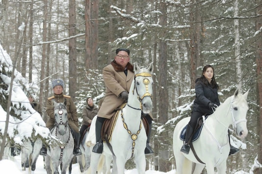 This undated photo provided on Wednesday, December 4, 2019, by the North Korean government shows North Korean leader Kim Jong Un, center, with his wife Ri Sol Ju, right, riding on white horse during his visit to Mount Paektu.