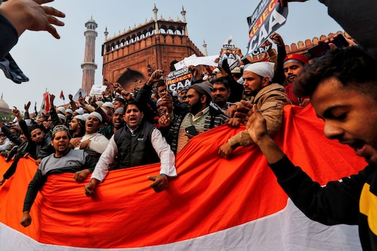 Demonstrators hold the national flag of India as they attend a protest against a new citizenship law, after Friday prayers at Jama Masjid (Reuters)