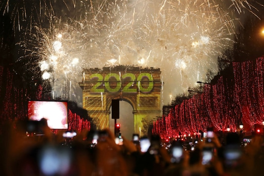 Revellers photograph fireworks over the Arc de Triomphe as they celebrate the New Year on the Champs Elysees, in Paris, France on January 1, 2020. (AP Photo/Christophe Ena)