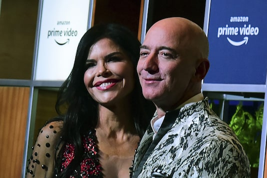 CEO of Amazon Jeff Bezos and his girlfriend Lauren Sanchez pose for pictures as they arrive to attend an event in Mumbai. (Image: AFP)