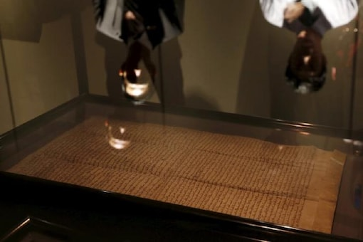 """Reflections of a security guard (L) and a visitor are seen on a glass as one of the few surviving copies of Magna Carta, Latin for """"The Great Charter"""" written in 1217 on sheep skin is displayed at an exhibition in Hong Kong, China. (Image: Reuters)"""