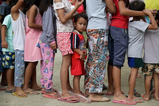 Children line for relief goods at an evacuation center in Tagaytay, Cavite province, southern Philippines. (Image: AP)