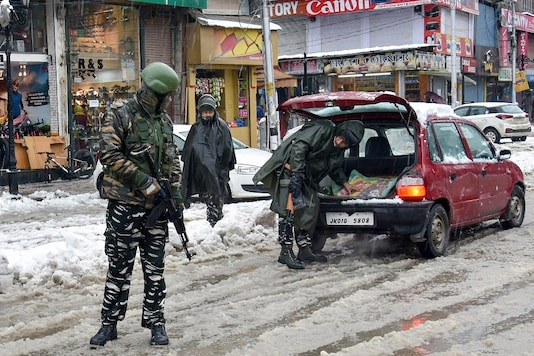 For representation: A security personnel checks a vehicle as others stand guard. (PTI/File photo)