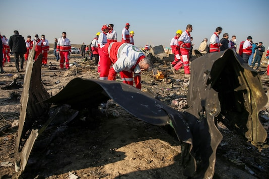 Red Crescent workers check the debris from the Ukraine International Airlines plane, that crashed after take-off from Iran's Imam Khomeini airport (Reuters)