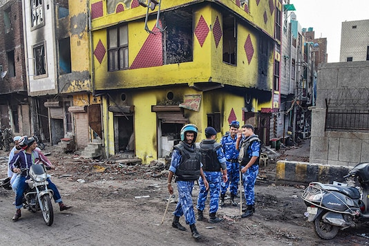 File Photo: Security personnel patrol a violence-affected area of Northeast Delhi. (Image: PTI)