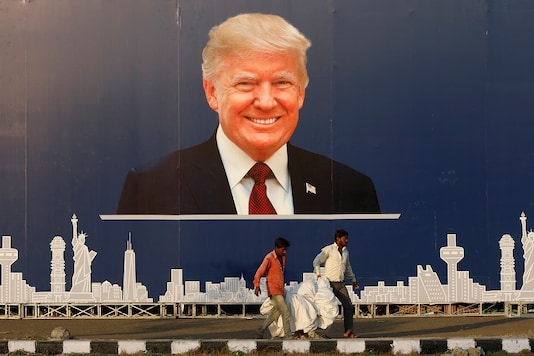 Workers walk past a hoarding of US President Donald Trump ahead of his visit in Ahmedabad on Saturday. (Reuters)