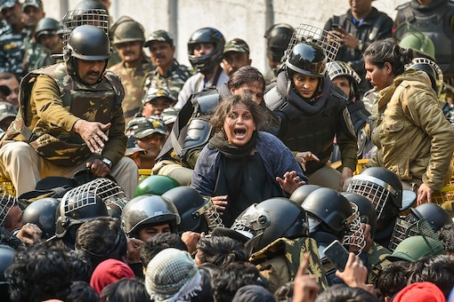 A woman protestor shouts as police stop many others during their march against the amended Citizenship Act, NRC and NPR, near Jamia Nagar in New Delhi,2020. (Image: PTI)
