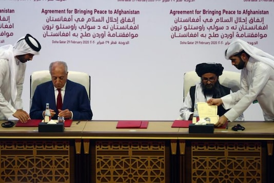 Mullah Abdul Ghani Baradar, the leader of the Taliban delegation, signs an agreement with Zalmay Khalilzad, U.S. envoy for peace in Afghanistan, at a signing agreement ceremony between members of Afghanistan's Taliban and the U.S. in Doha, Qatar. (Reuters)