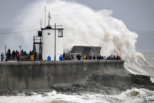 People watch waves and rough seas pound against the harbour wall at Porthcawl in Wales, as Storm Dennis sweeps across the country. (AP)