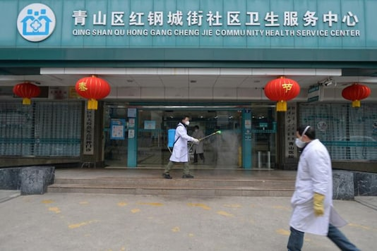 A doctor disinfects the entrance of a community health service centre in Qingshan district of Wuhan. (Reuters)
