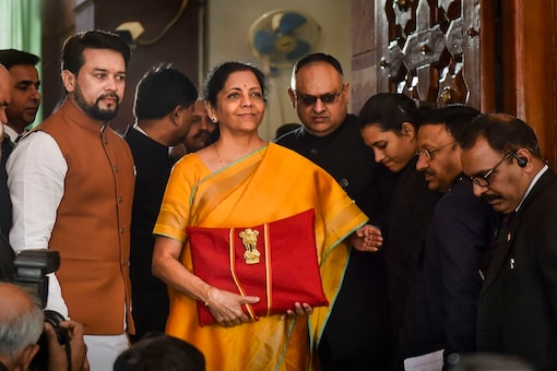 Finance Minister Nirmala Sitharaman, flanked by her deputy Anurag Thakur (to her right) and a team of officials, shows a folder containing the Union Budget documents on her arrival at Parliament in New Delhi, Saturday. (PTI Photo)