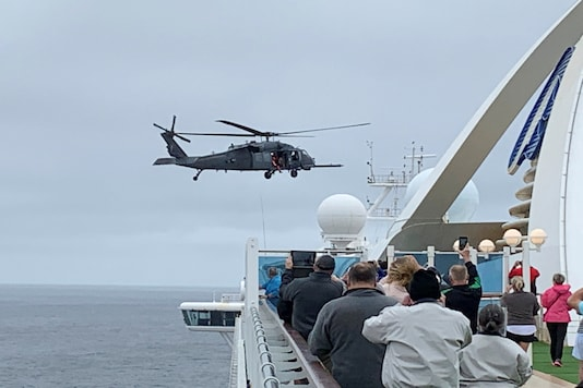 Passengers on board the Grand Princess cruise ship, which had previously carried two passengers who contracted the coronavirus, watch while a US military helicopter hovers above the deck, as they approach their original destination of San Francisco, California, US March 5, 2020. Courtesy of Steve Berry/Handout via REUTERS
