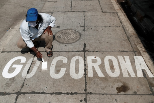 A man paints a message on a street after India ordered a 21- day nationwide lockdown to limit the spreading of coronavirus disease (COVID-19) in Mumbai, India March 28, 2020. REUTERS/Francis Mascarenhas